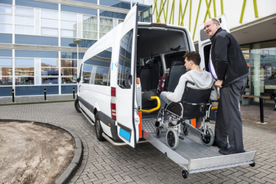 The driver of a wheel chair taxi, helping a disabled men in a wheel chair, using the lift in the back of his mini van Photo Taken On: March 13th, 2017