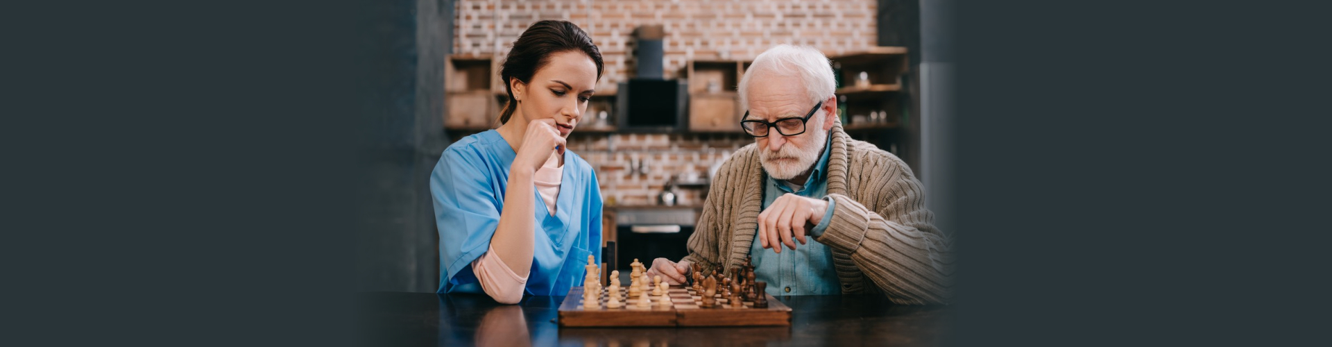 senior man and female caregiver playing chess