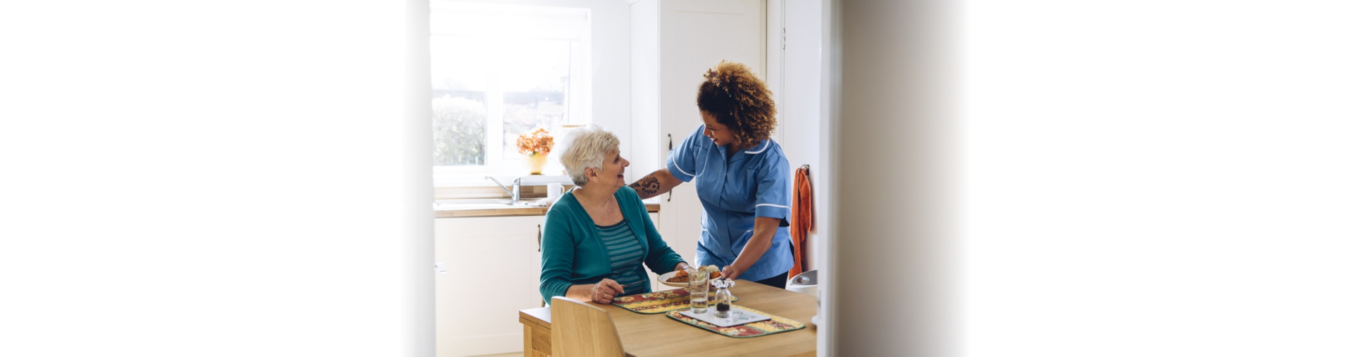 Care worker giving senior woman her dinner in her home.